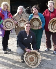 Group of people holding up their handmade baskets